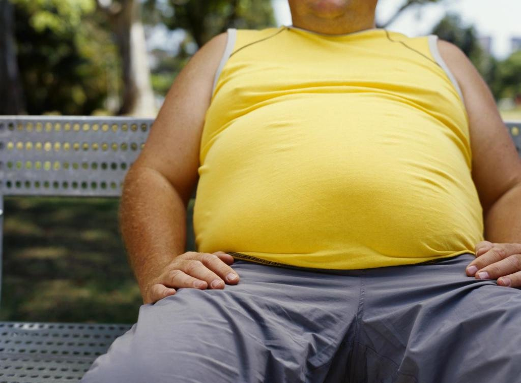 толстый мужчина в желтой майке на скамейке